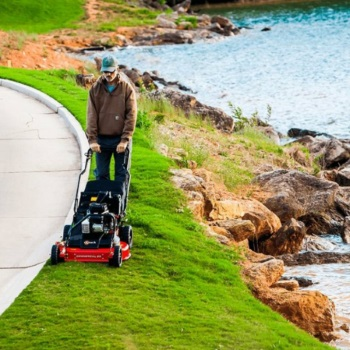 man cutting grass with an exmark push mower near water's edge