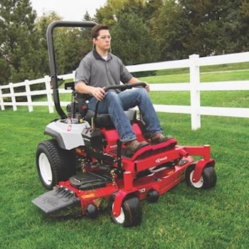 Exmark zero turn mower driving by white fence