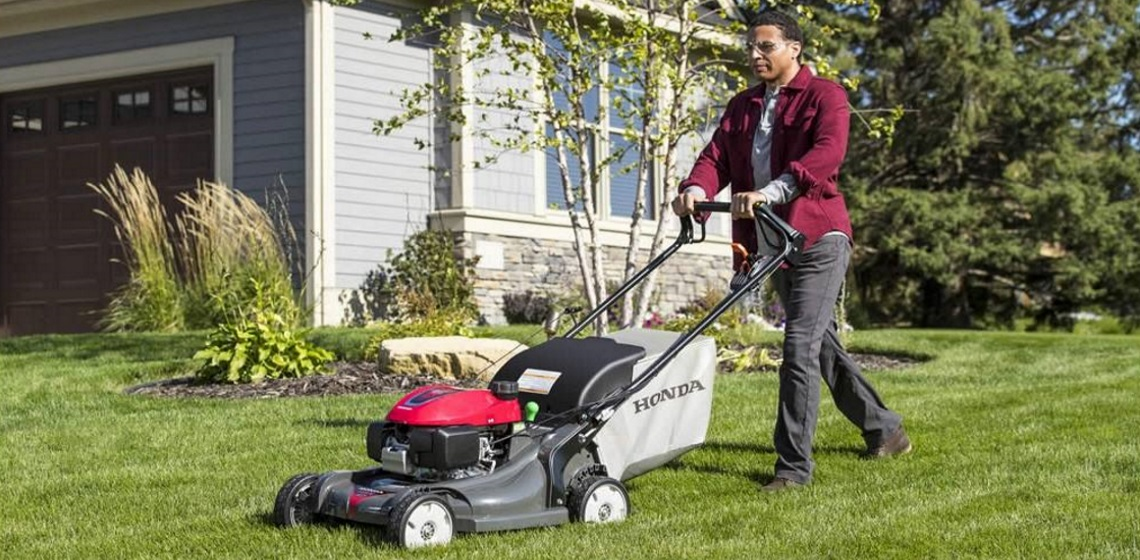 a man using a Honda Power Equipment HRX217HYA push mower