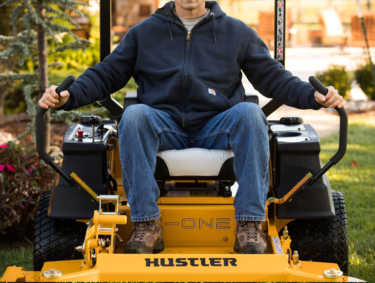 Man riding a Hustler Turf Mower